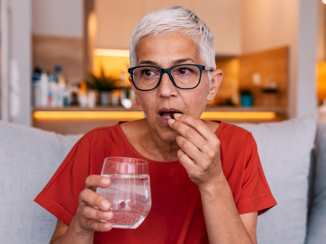a woman taking Appetite stimulants with water