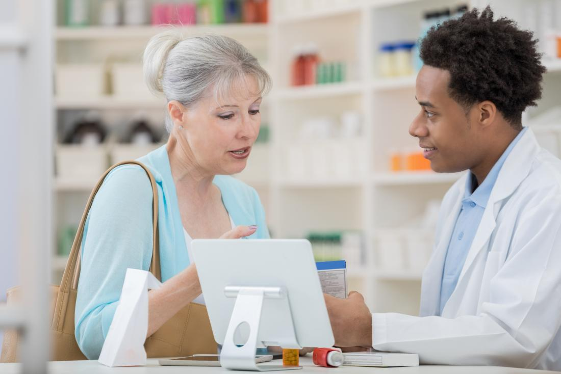 a woman picking up her prescription for glimepiride