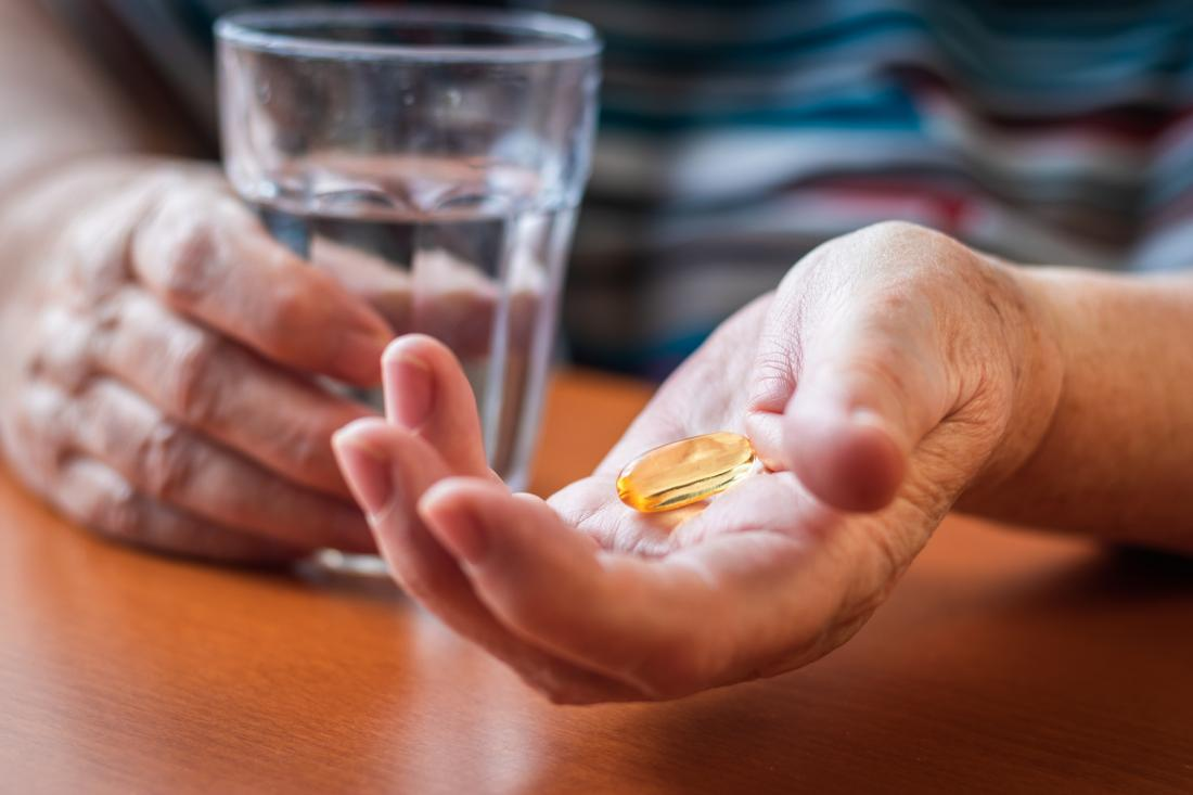close up of woman taking fish oil capsules