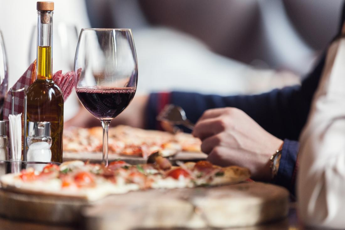 a woman enjoying wine with a pizza