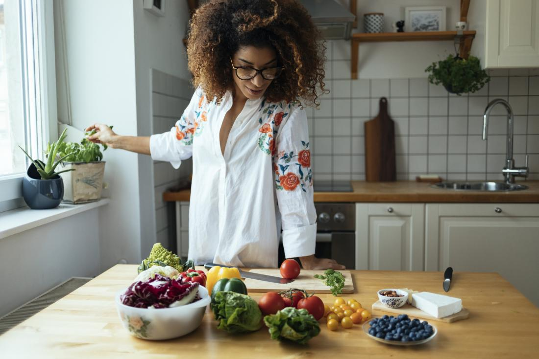 woman contemplating vegetables