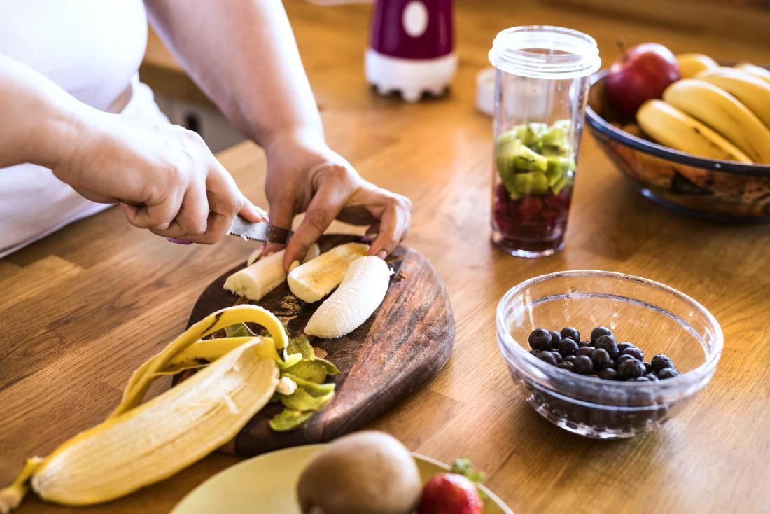 person chopping or cutting fruits for smoothie or juice including banana kiwi and blueberries