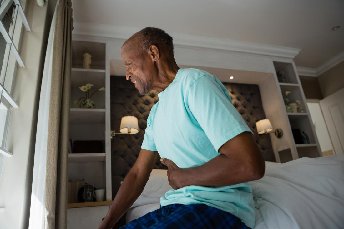 man with aortic dissection suffering from abdominal pain sitting on bed clutching stomach