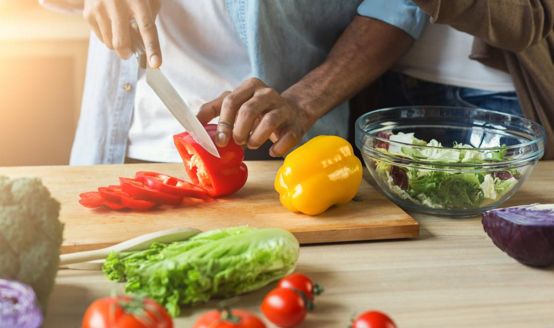 close up of man chopping vegetables
