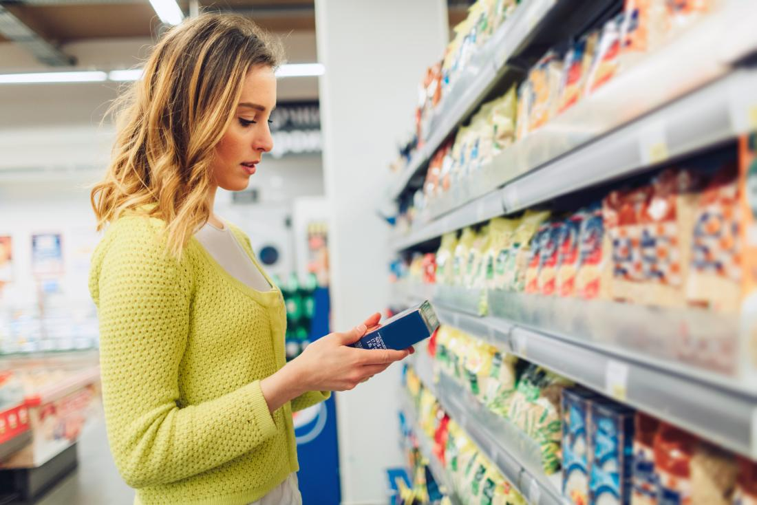 a woman looking at a gluten free item a supermarket as it may be good for her diabetes