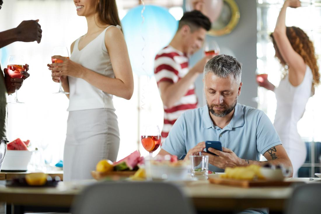man checking his phone at party