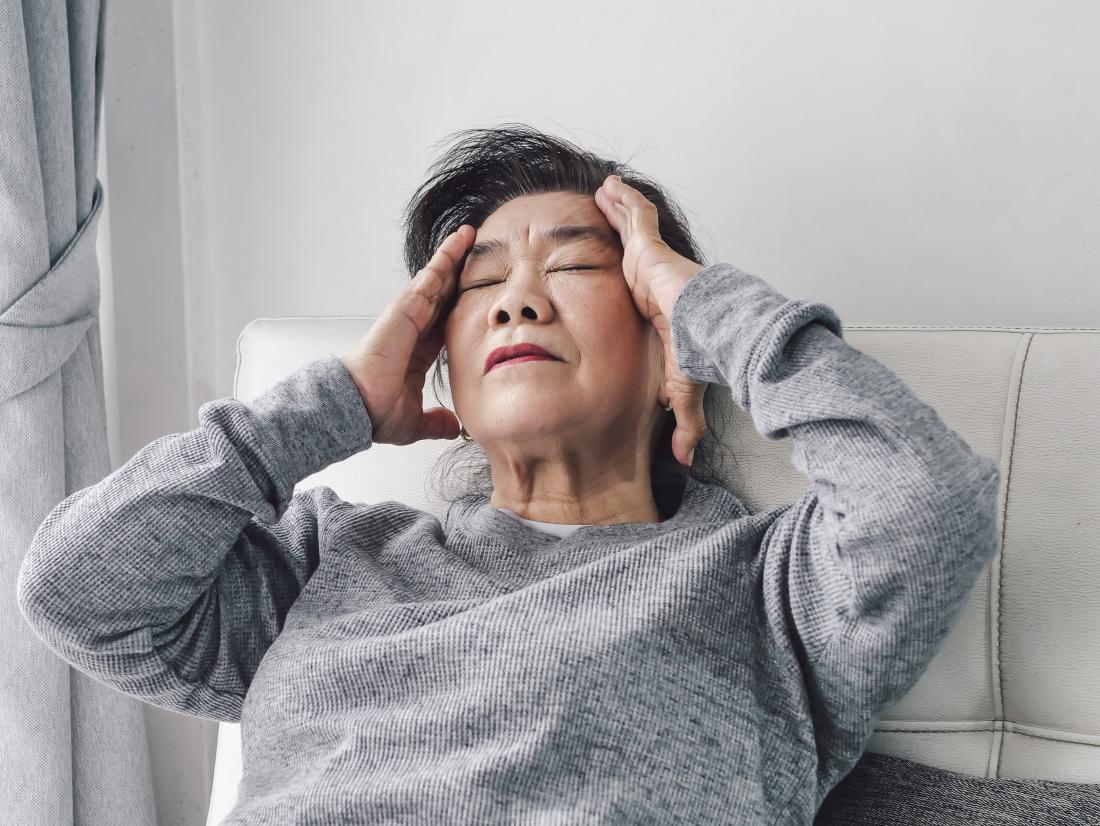 an elderly asian lady experiencing a headache.