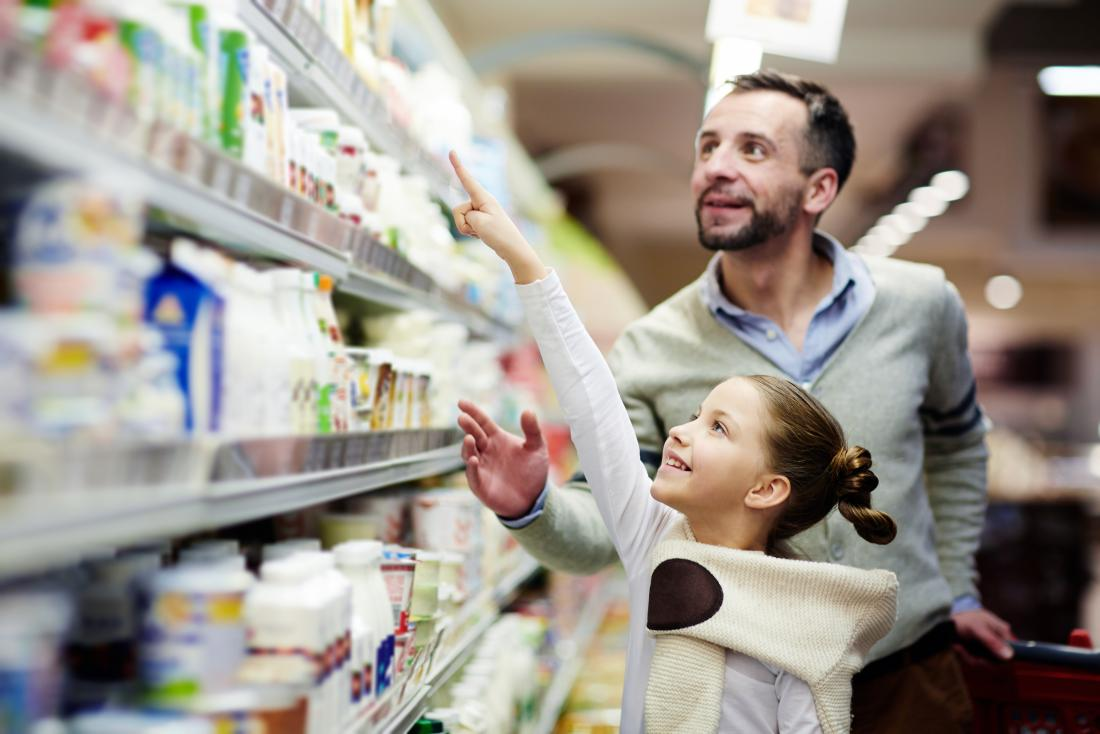 a man and his daughter choosing yogurt in a shop