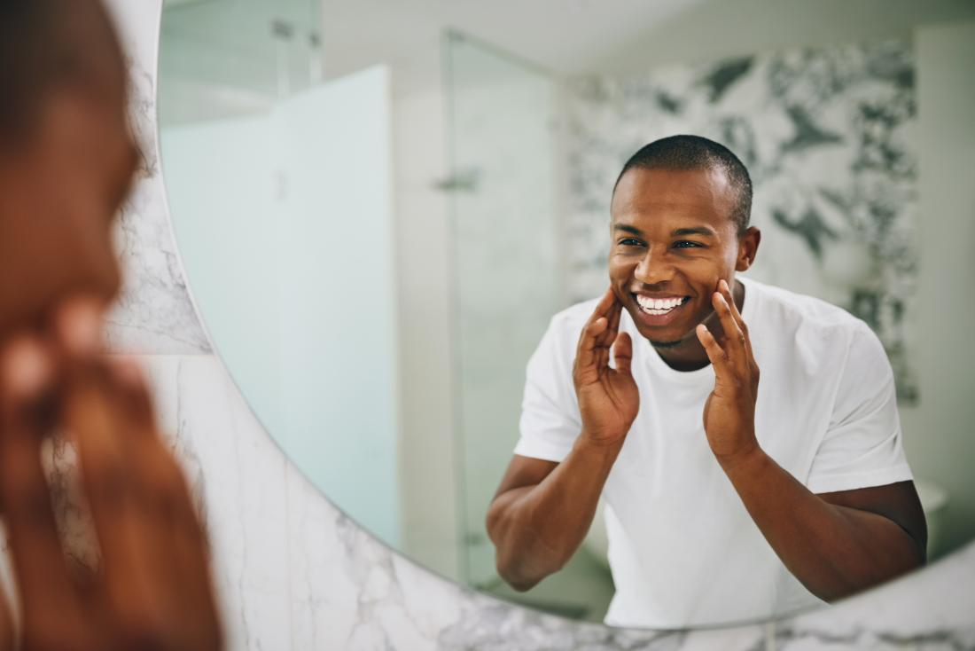 Man touching skin smiling int mirror