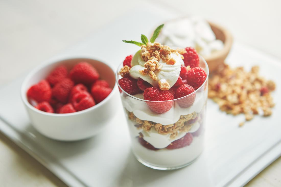 Raspberries, muesli, and yoghurt in cup for healthy breakfast or snack