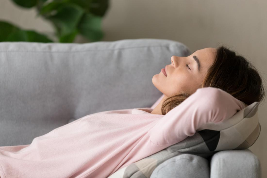 woman lying on the sofa and deep breathing to help with chest burning