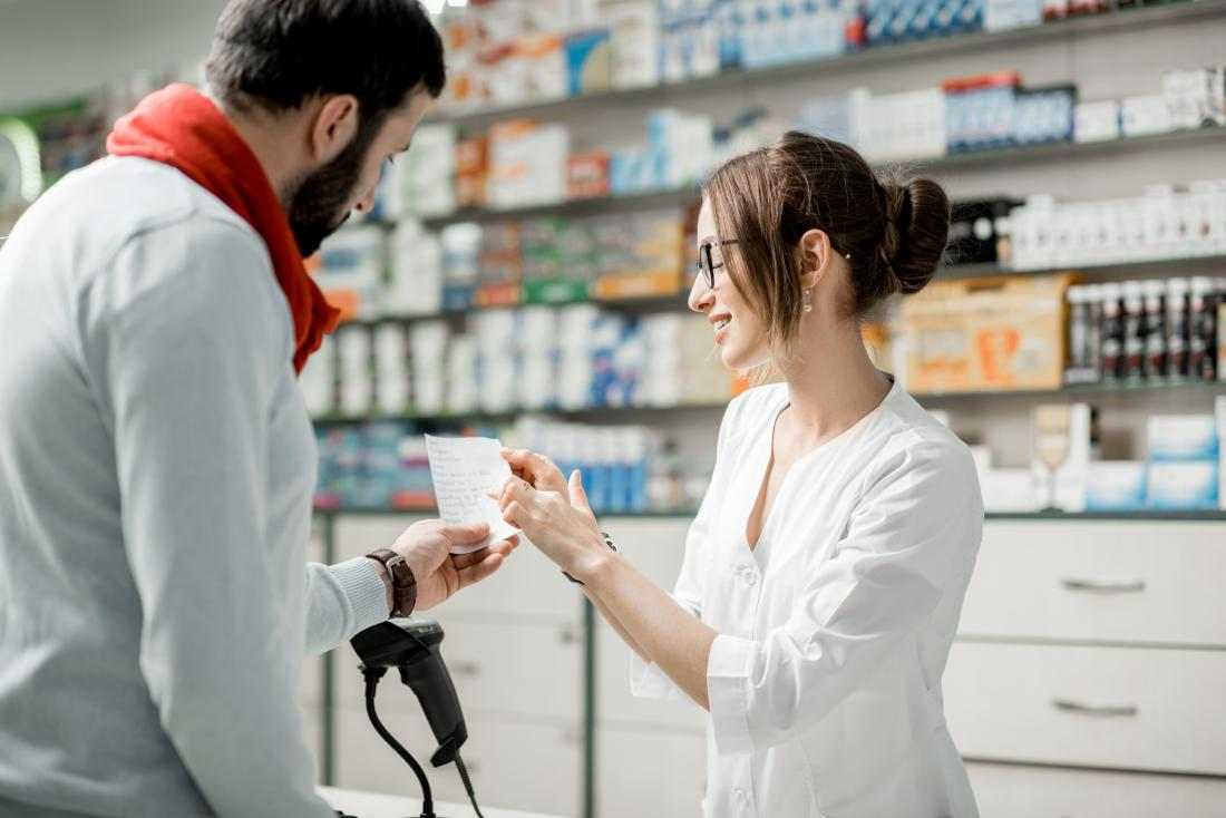 a man looks at his prescription with a pharmacist