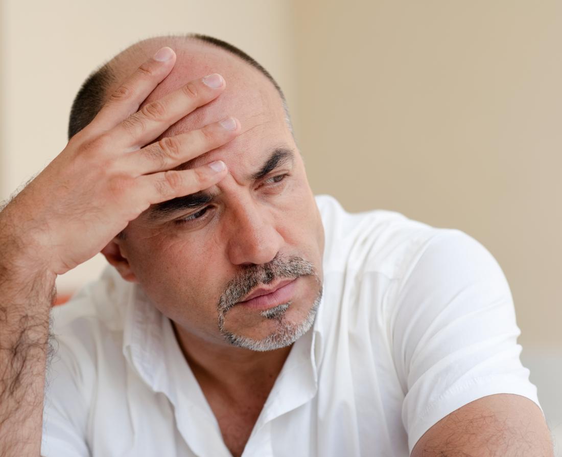 a bald man experiencing a headache.