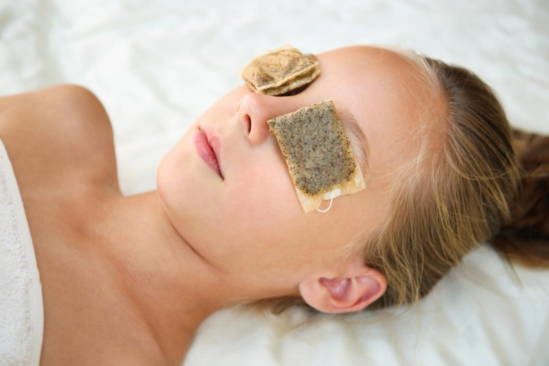a woman with Tea bags on her eyes for health benefits.