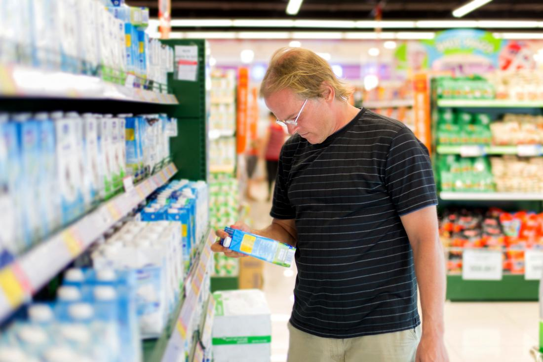man looking at non dairy milk in supermarket