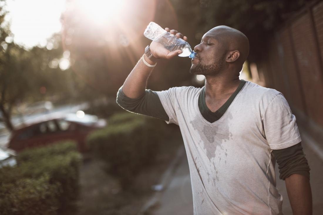 a man experiencing painful respiration and excessive sweating drinks from a water bottle outside