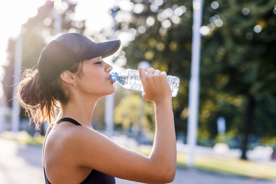 a woman hydrating with water during exercise.