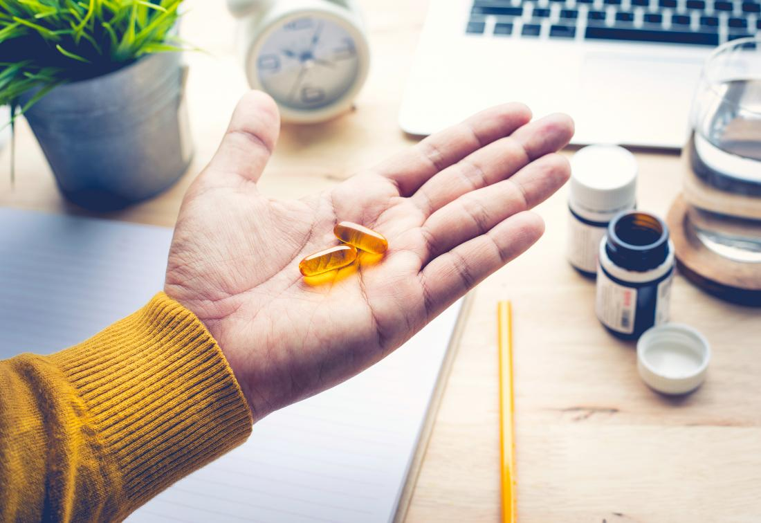 person at desk holding omega 3 supplements in palm