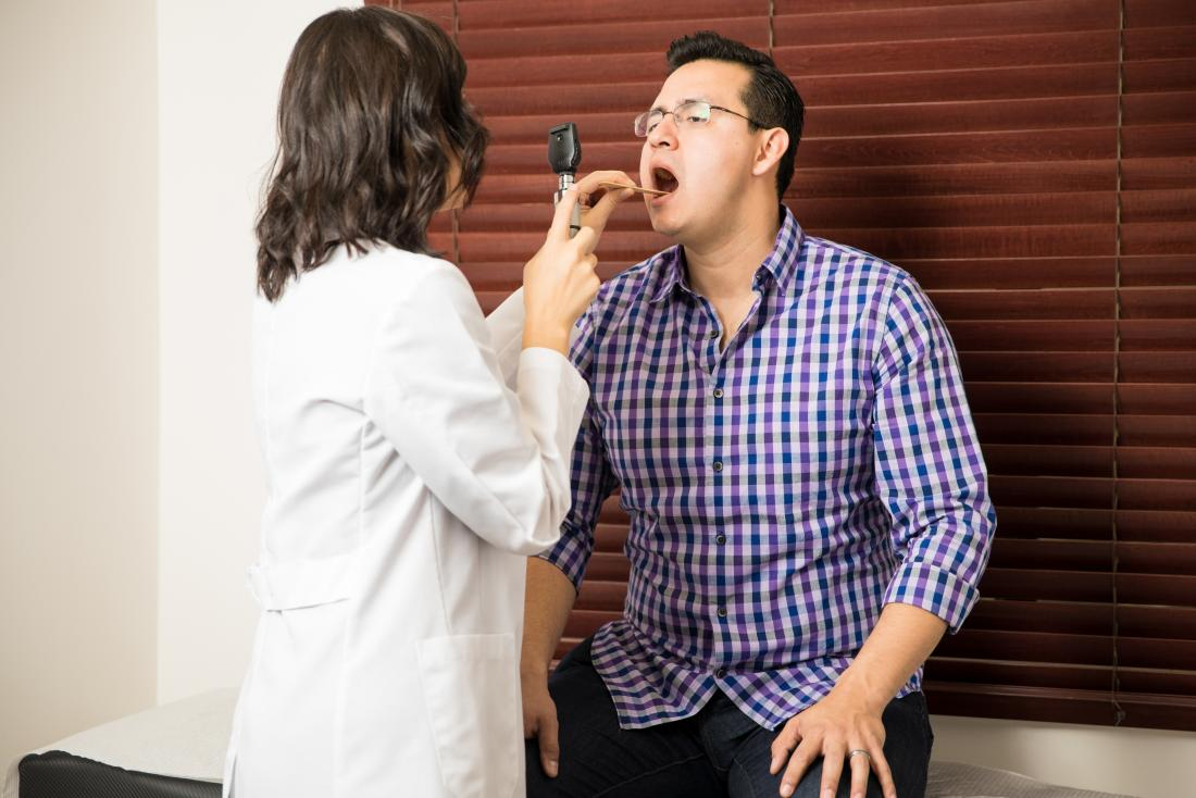 man having his throat inspected by a doctor
