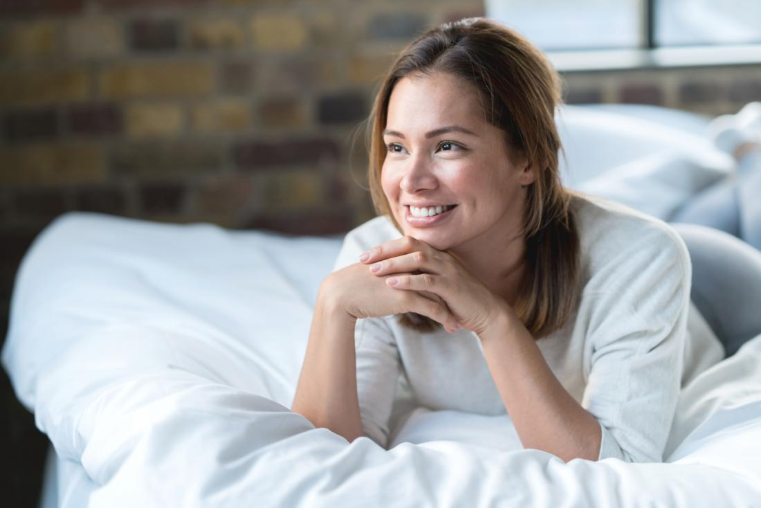 a happy looking woman lying on a bed.