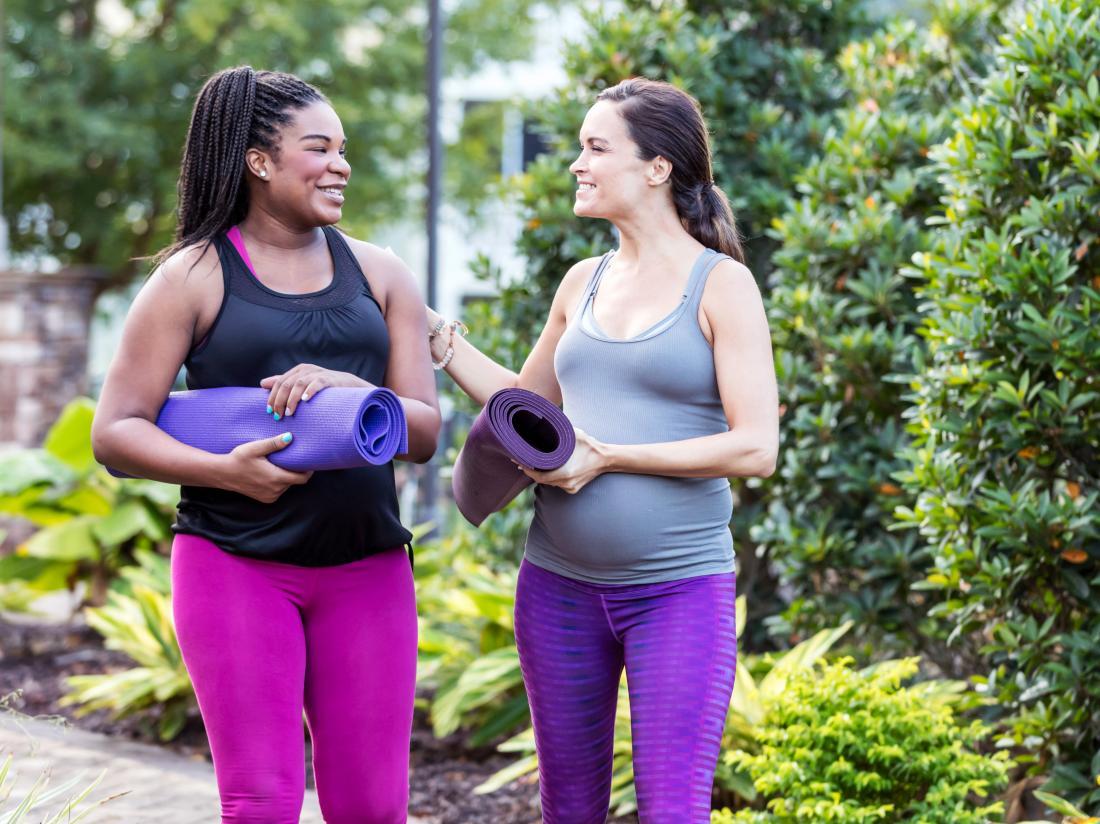 two woman walking talking and carrying yoga mats