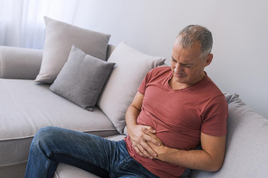 a man getting stomach cramps on his sofa