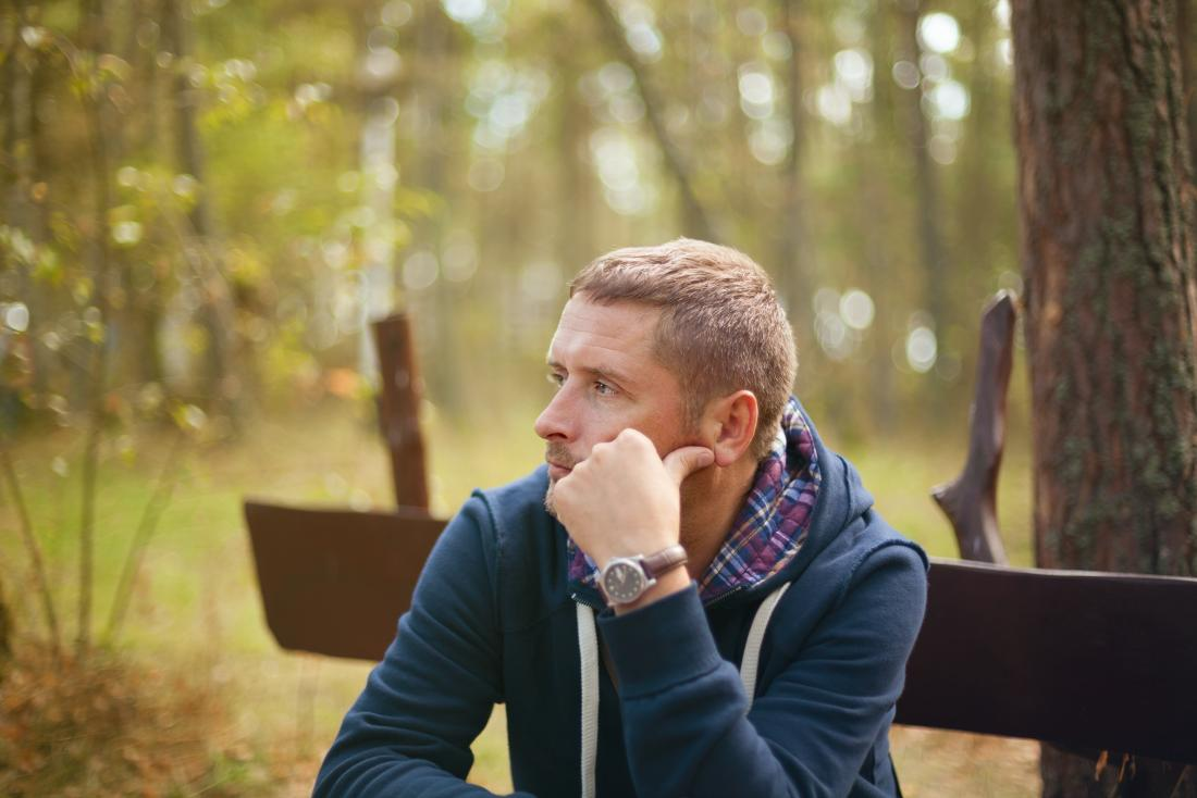a man with PTSD looking depressed whilst sat in a park.