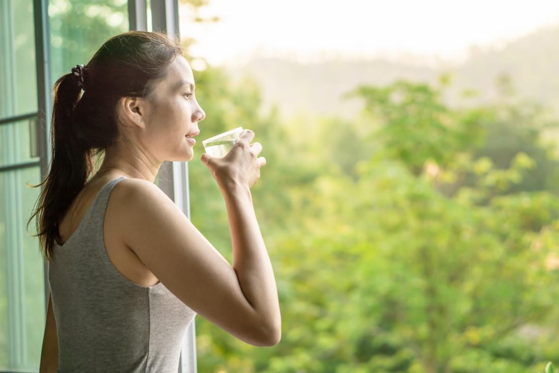 woman drinking a glass of water which is good for kidneys