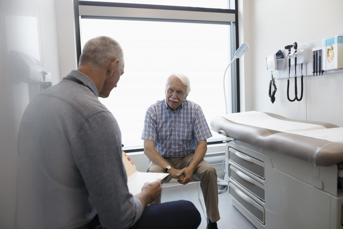 senior man sitting in doctor s office while gp looks at notes