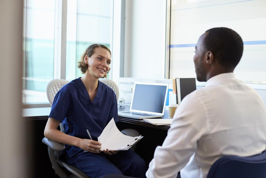 man talking to doctor in her office both smiling