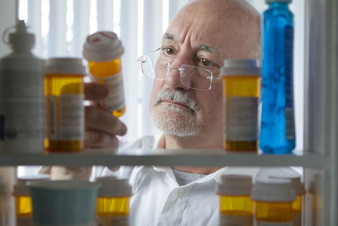 Senior man looking at prescription drugs in a medicine cabinet.
