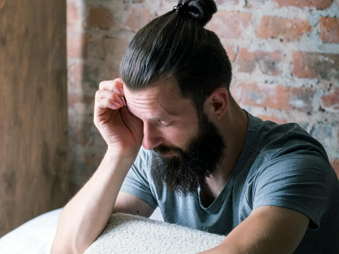 a man with a manbun experiencing drowsiness and a headache.