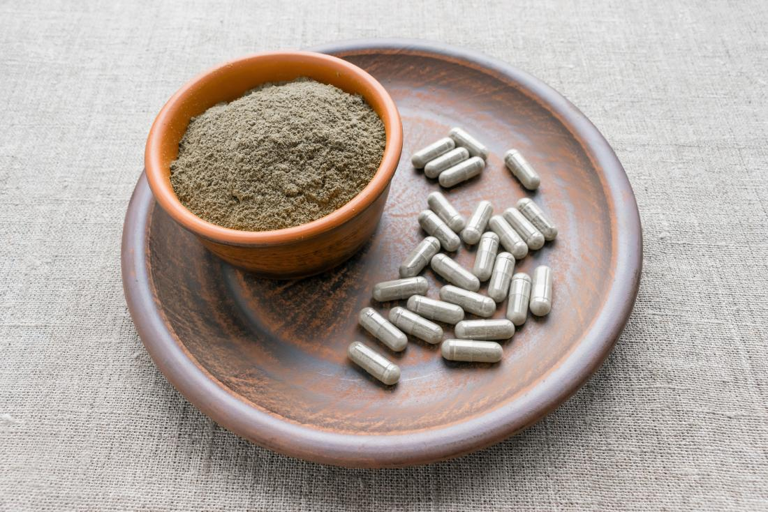 Triphala capsules and powder on clay plate that could give a person benefits