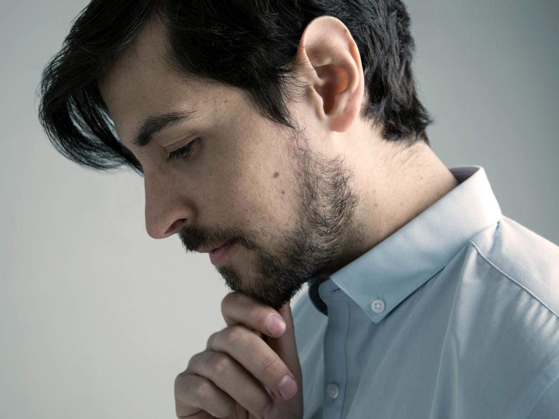 a man looking pensive about his penis sores.