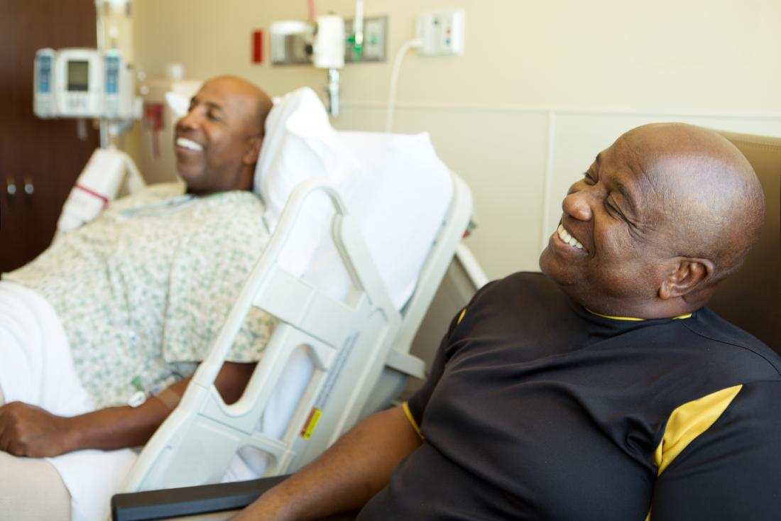 a man in hospital with his smiling son sat next to him.