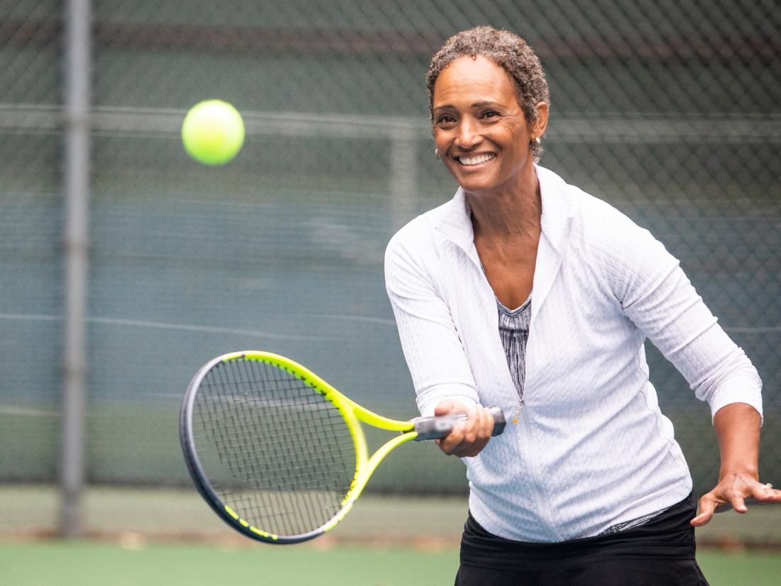 a senior woman playing tennis with a smile