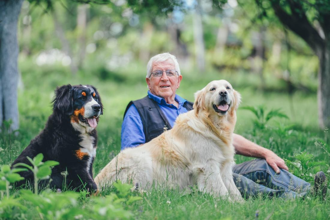 man sitting with two dogs