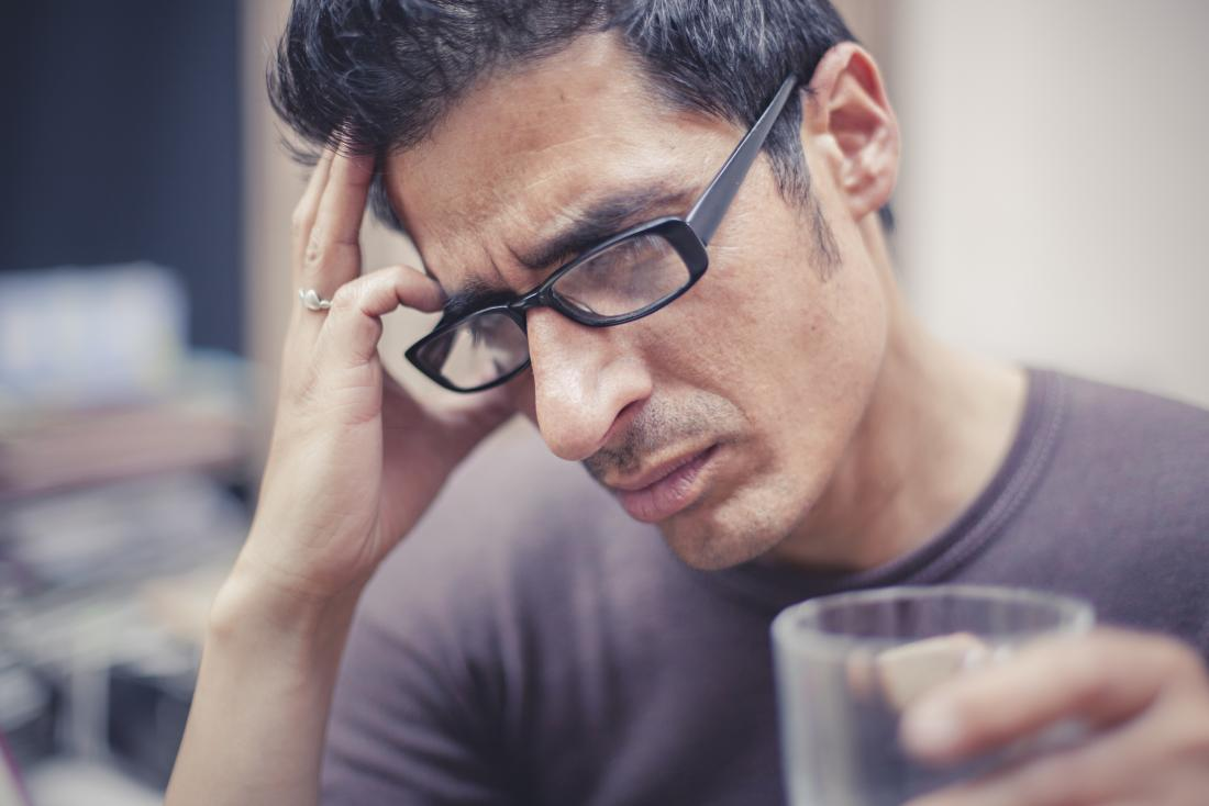 man with headache on right side of head holding head and holding glass