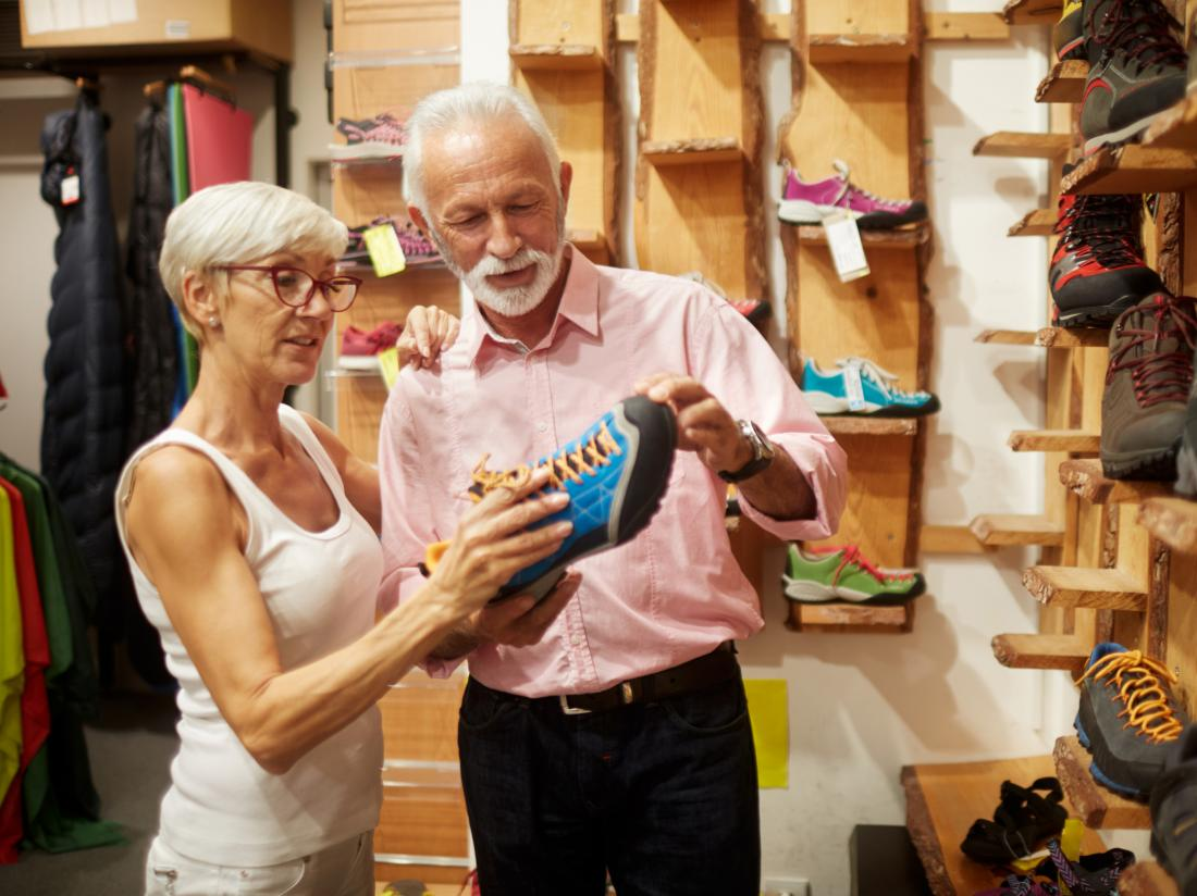 a man and woman looking at a shoe in a shoe shop