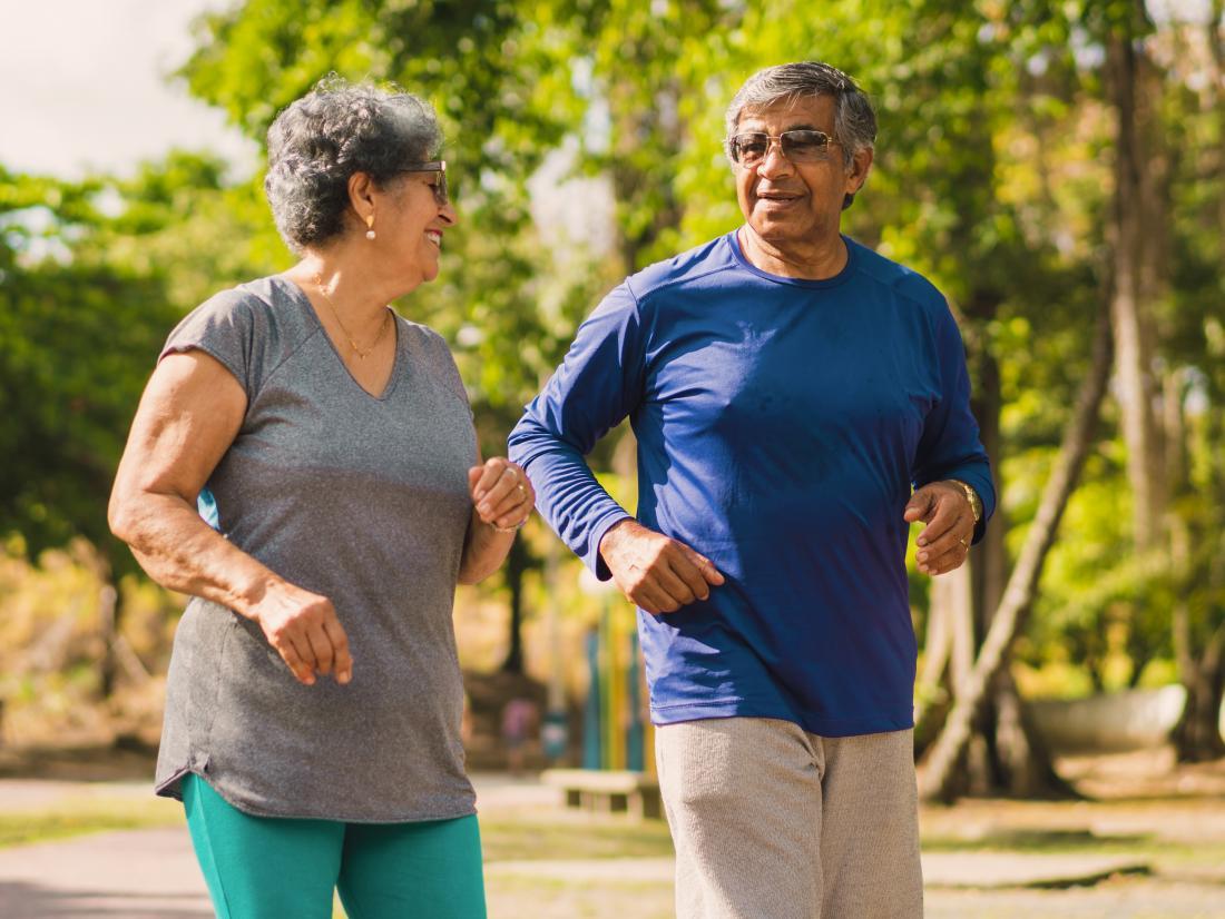 a senior couple having a gentle jog in the park.