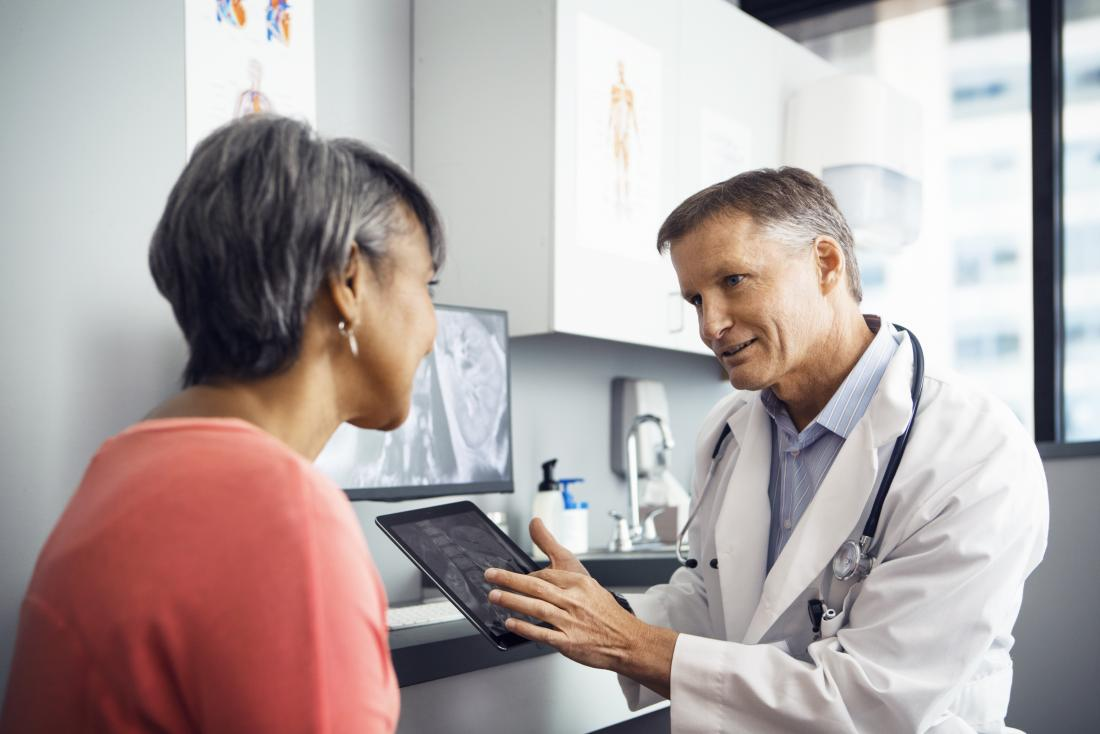doctor speaking to patient in office while showing them a tablet