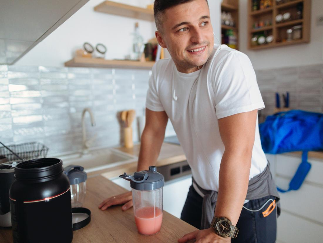 a man smiling in a kitchen next to a protein shake.