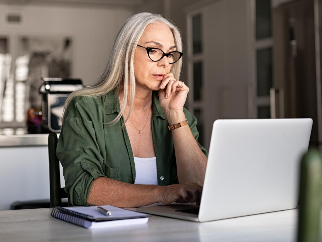 a senior woman sat at a computer