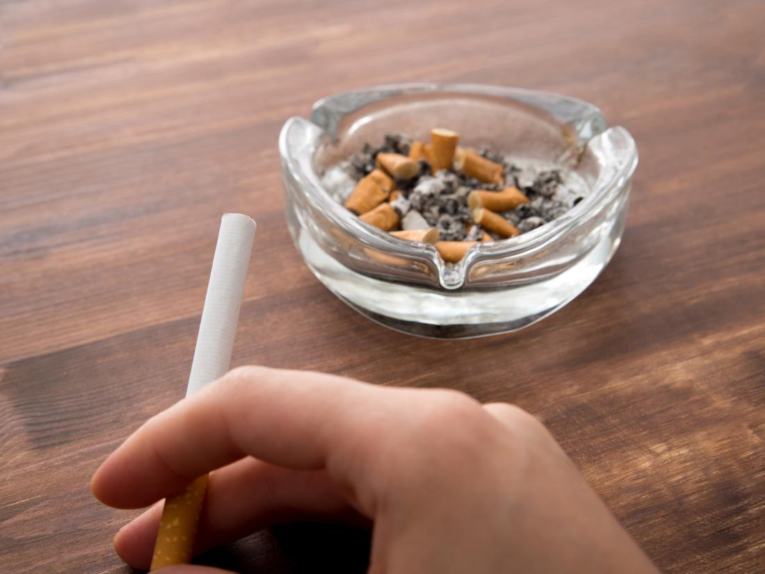 cigarette in a persons hand and an ash tray with butts in it.
