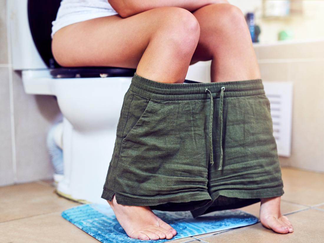 a woman sat on the toilet who may have clear urine.