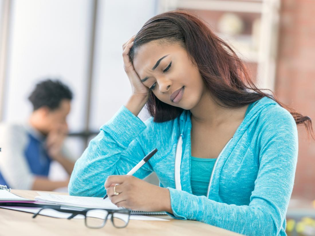a young woman struggling to write.