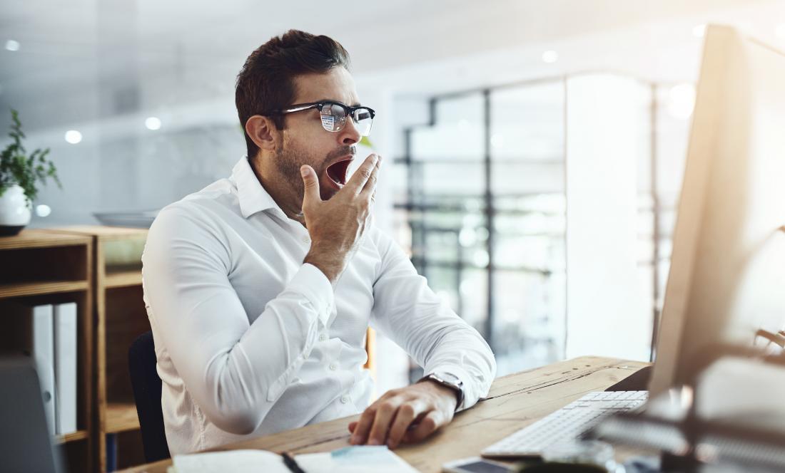 a man at work yawning at his desk