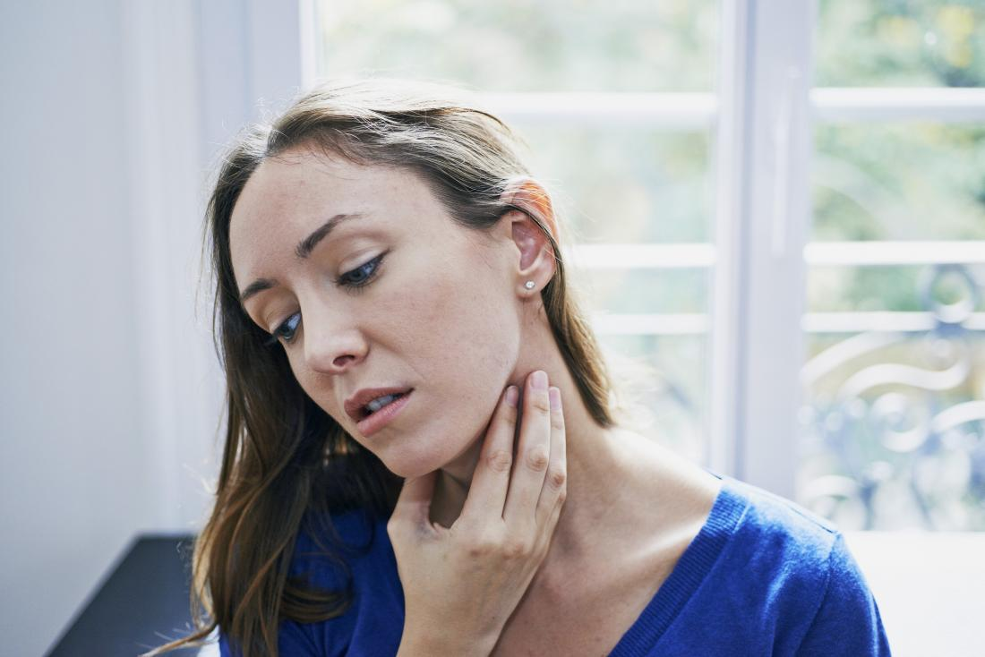 woman with sore throat holding neck in pain
