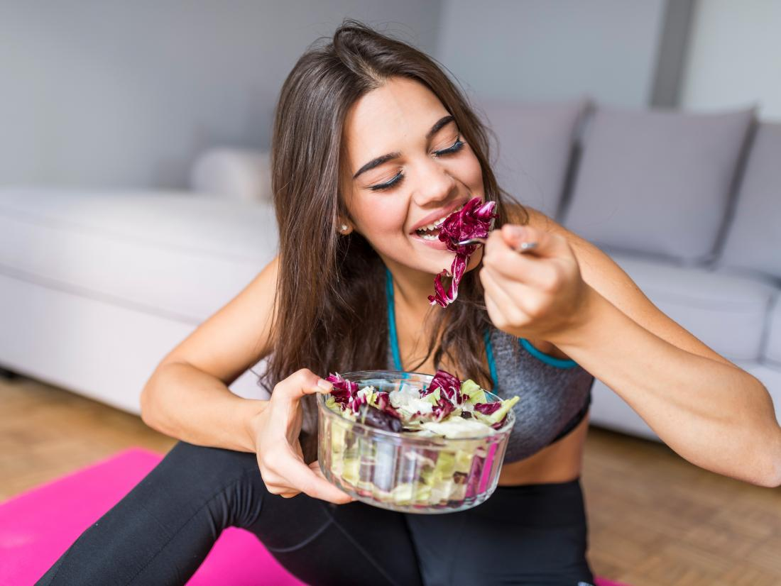 a woman eating a salad after a workout