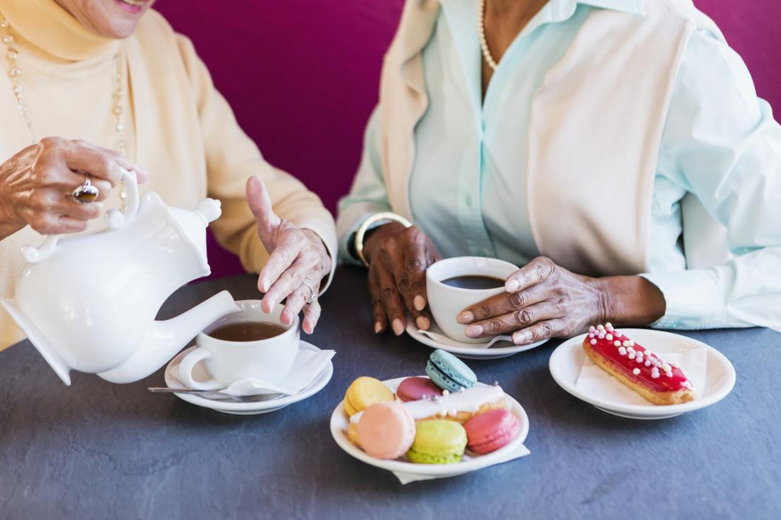 close up of women eating pastry and drinking coffee